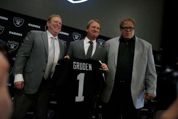 Jon Gruden (center), Oakland Raiders head coach, holds an Oakland Raiders jersey with his name as he stands between Oakland Raiders owner Mark Davis (left) and Oakland Raiders  general manager Reggie McKenzie (right), after being introduced as the new head coach of the Oakland Raiders at Raiders Headquarters on Tuesday, January 9, 2018 in Alameda, Calif.