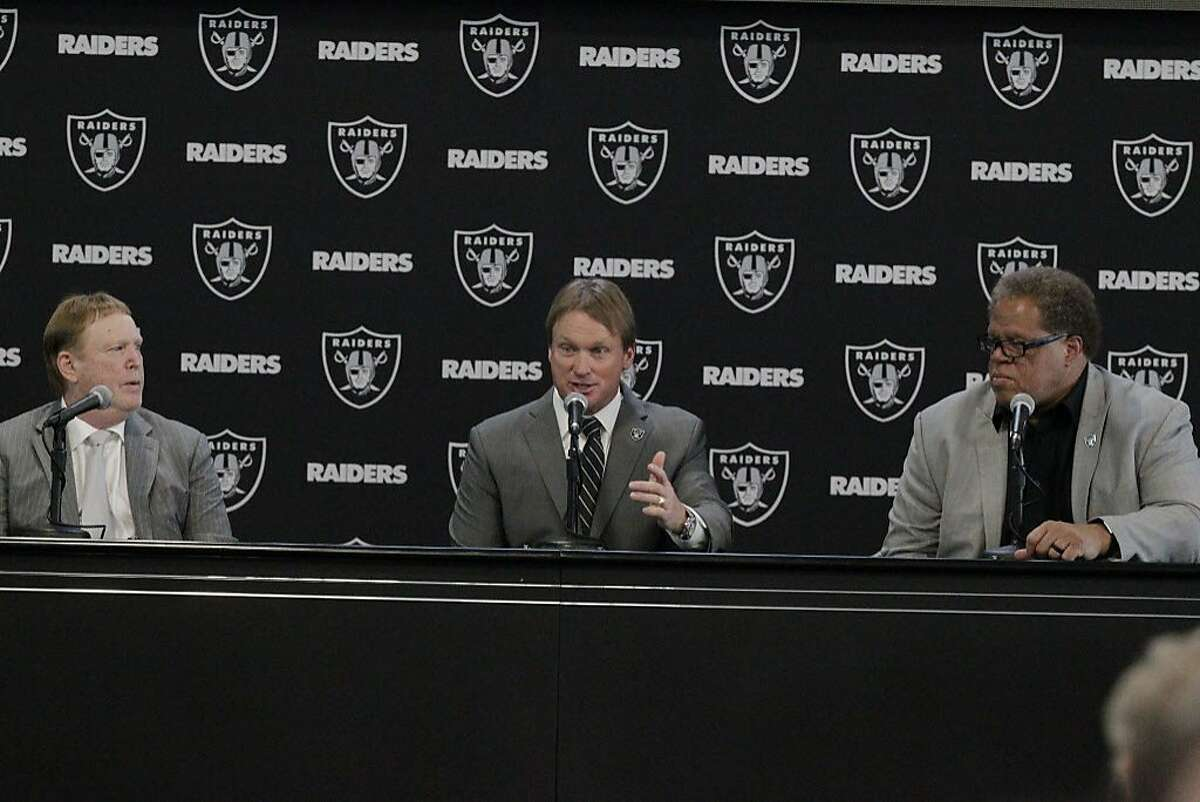 Jon Gruden (center), Oakland Raiders head coach, sits between Oakland Raiders owner Mark Davis (left) and Oakland Raiders general manager Reggie McKenzie (right), after being introduced as the new head coach of the Oakland Raiders at Raiders Headquarters on Tuesday, January 9, 2018 in Alameda, Calif.