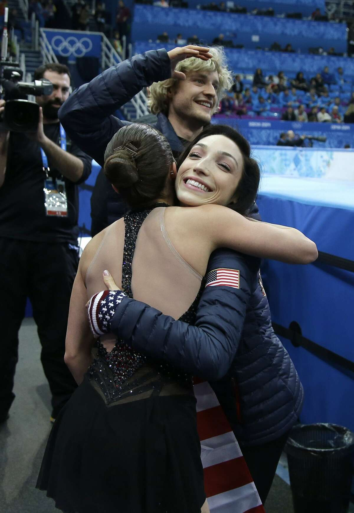 US US Marissa Castelli (C) is congratulated by US Meryl Davis (R) and US Charlie White (top) in the kiss and cry zone the Figure Skating Pairs Team Short Program at the Iceberg Skating Palace during the Sochi Winter Olympics on February 6, 2014. AFP PHOTO / POOL / DARRON CUMMINGSDARRON CUMMINGS/AFP/Getty Images
