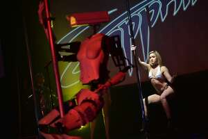 TOPSHOT - A human dancer performs next to a stripper robot at the Sapphire Gentlemen's Club on the sidelines of CES 2018 in Las Vegas on January 8, 2018. / AFP PHOTO / MANDEL NGAN        (Photo credit should read MANDEL NGAN/AFP/Getty Images)