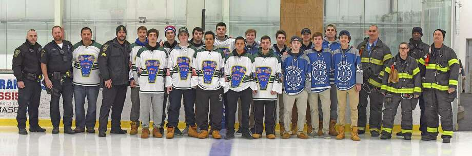"""Senior members of the Norwalk-McMahon co-op joined the Staples captains for a photo with Norwalk police officers and firemen after they handed out special """"Police"""" and """"Fire"""" department jerseys for next Saturday's benefit game at the SoNo Ice House in Norwalk. Photo: John Nash / Hearst Connecticut Media / Norwalk Hour"""
