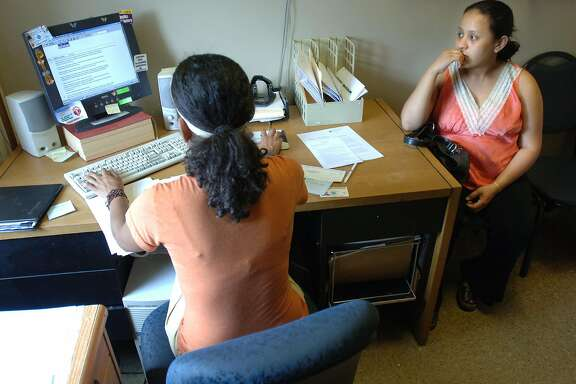 A Salvadoran woman (right) in the U.S. on Temporary Protected Status after losing her home in the 2001 earthquake gets help with her work permit. On Monday, the Trump administration announced an end to the program for about 200,000 Salvadorans.