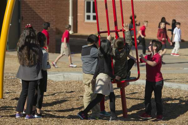 Students at Bowie Elementary play on playground equipment and run around 12/19/17. Tim Fischer/Reporter-Telegram
