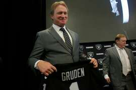Jon Gruden (l to r), Oakland Raiders head coach, holds a Oakland Raiders jersey with his name as he stands next to owner Mark Davis after being introduced as the new head coach of the Oakland Raiders during a news conference at Raiders Headquarters on Tuesday, January 9, 2018 in Alameda, Calif.
