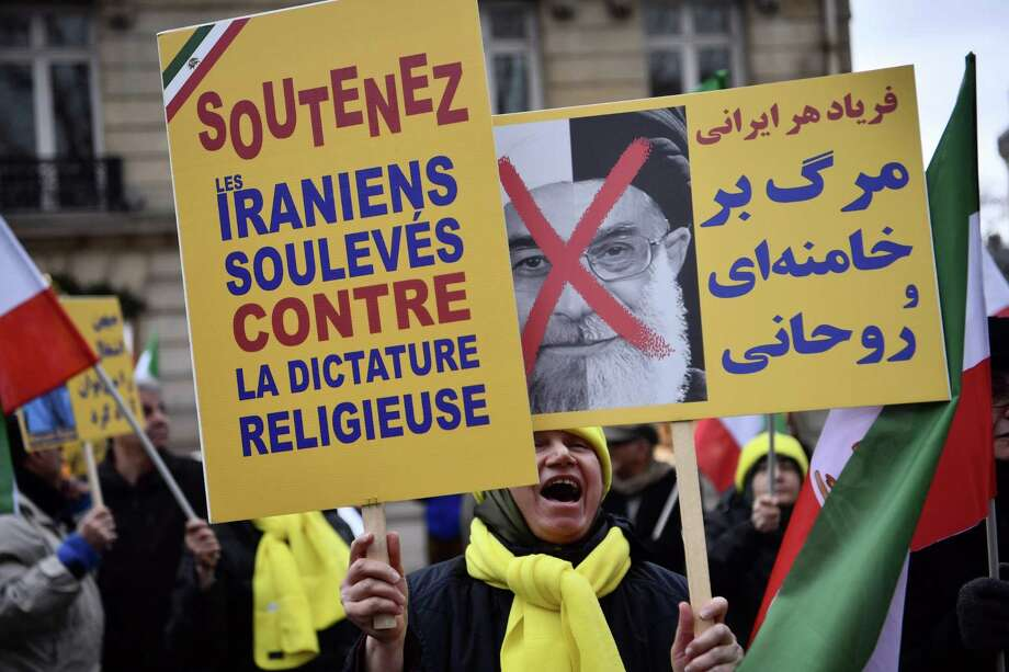"""Protesters hold placards reading """"Support Iranians risen up against the religious dictatorship"""" and a portrait of Iranian President Hassan Rouhani with a red cross mark over it during a demonstration in support of the Iranian people amid a wave of protests spreading throughout Iran, on Jan. 5 in Paris. Violent demonstrations have rocked Iran since Dec. 28, with protests that started over the economy turning against the Islamic regime as a whole. Photo: CHRISTOPHE SIMON /AFP /Getty Images / AFP or licensors"""