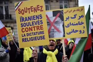 """Protesters hold placards reading """"Support Iranians risen up against the religious dictatorship"""" and a portrait of Iranian President Hassan Rouhani with a red cross mark over it during a demonstration in support of the Iranian people amid a wave of protests spreading throughout Iran, on Jan. 5 in Paris. Violent demonstrations have rocked Iran since Dec. 28, with protests that started over the economy turning against the Islamic regime as a whole."""