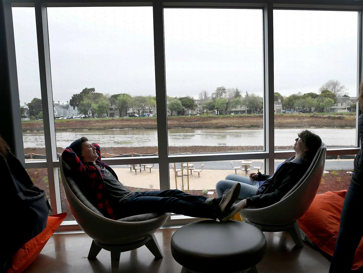 Hayden Navarro (left) and Natalie Cheyette settle in on lounge chairs with a view overlooking Belmont Slough as students explore the new Design Tech High School on the Oracle campus in Redwood City, Calif. on Tuesday, Jan. 9, 2018.