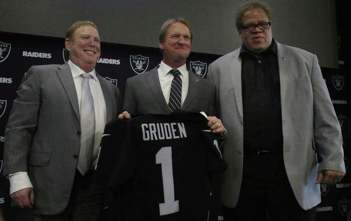 Owner Mark Davis (left), head coach Jon Gruden and general manager Reggie McKenzie pose for the cameras after Gruden was reintroduced to the Bay Area at a news conference in Alameda.