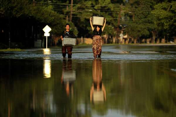 File- This Sept. 4, 2017, file photo shows Mariko Shimmi, right, helping carry items out of the home of Ken Tani in a neighborhood still flooded from Hurricane  Harvey in Houston. Thursday, Nov. 30, 2017,  was the last day of an intense and destructive hurricane season that included 17 named storms, 10 of which became hurricanes. The 2017 Atlantic hurricane season will be remembered for a deadly trio of storms, Harvey, Irma and Maria, that ravaged Texas, Florida, Puerto Rico and numerous other islands. The storms killed at least 441 people and did about $369 billion in damage.(AP Photo/Gregory Bull, File)