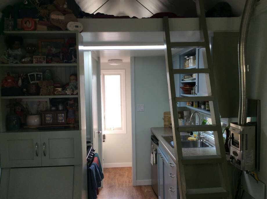 The ladder leads up to a small loft above the kitchen where Aileen Brown sleeps on a twin-sized mattress.Click through this slideshow for more pictures of the tiny home. Photo: Aileen Brown