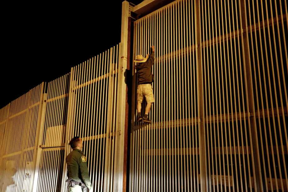 Eduardo Olmos, 38, U.S. Border Patrol agent, apprehends a Mexican immigrant trying to climb the secondary fence into Border Field State Park, San Diego, Calif. from Playas de Tijuana, along the U.S.-Mexico border in San Diego, Calif., on July 31, 2017. (Gary Coronado/Los Angeles Times/TNS) Photo: Gary Coronado, MBR / TNS / Los Angeles Times