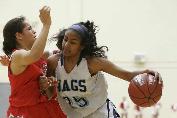 Lee's Jenesis Navarro (left) defends Johnson's Deja Kelly (25) in girls basketball at Littleton Gym on Tuesday, Jan. 8, 2018. Navarro scored a game-high 37 points to give Lee the victory over Johnson, 76-51, in district play. (Kin Man Hui/San Antonio Express-News)