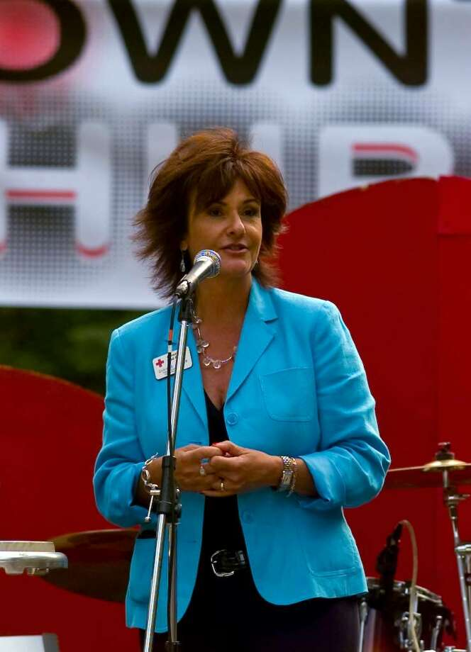 The Special O Band performed in the first Downtown Thursdays concert series on McLevy Green in downtown Bridgeport, Conn. on Thursday July 01, 2010. Here, Dianne Auger, CEO of the Connecticut Region of the American Red Cross, lets concert goes know they are raising funds during the concert to help tornado victims. Photo: Christian Abraham / Connecticut Post