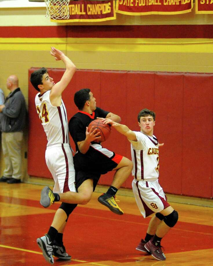 St. Joseph's Ace Luzietti, right, blocks Fairfield Warde's Jeff Seganos Jr., center, during basketball action in Trumbull, Conn., on Tuesday Jan. 9, 2018. Defending at left is St. Joe's Ian Argento. Photo: Christian Abraham / Hearst Connecticut Media / Connecticut Post
