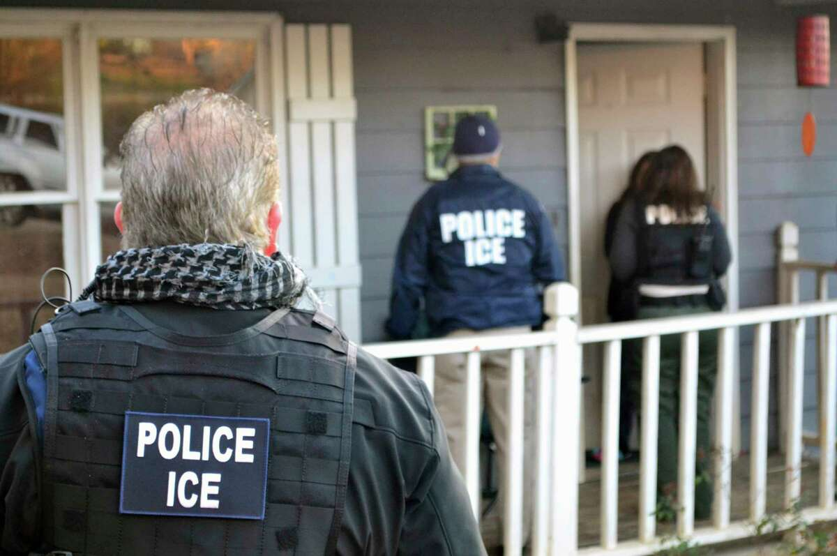 In this Feb. 9, 2017, photo provided U.S. Immigration and Customs Enforcement, ICE agents at a home in Atlanta, during a targeted enforcement operation aimed at immigration fugitives, re-entrants and at-large criminal aliens.