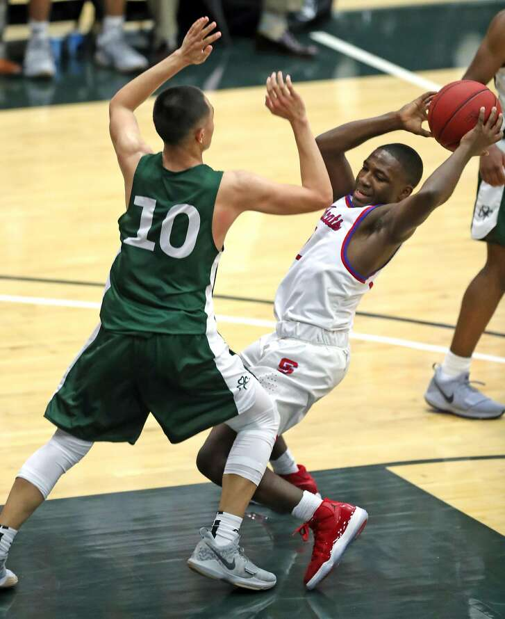 St. Ignatius' Darrion Trammell is defended by Sacred Heart Cathedral's John Lawvan Johns during 1st quarter of Bruce Mahoney boys' basketball game at USF War Memorial Gymnasium in San Francisco, Calif., on Monday, January 9, 2018.