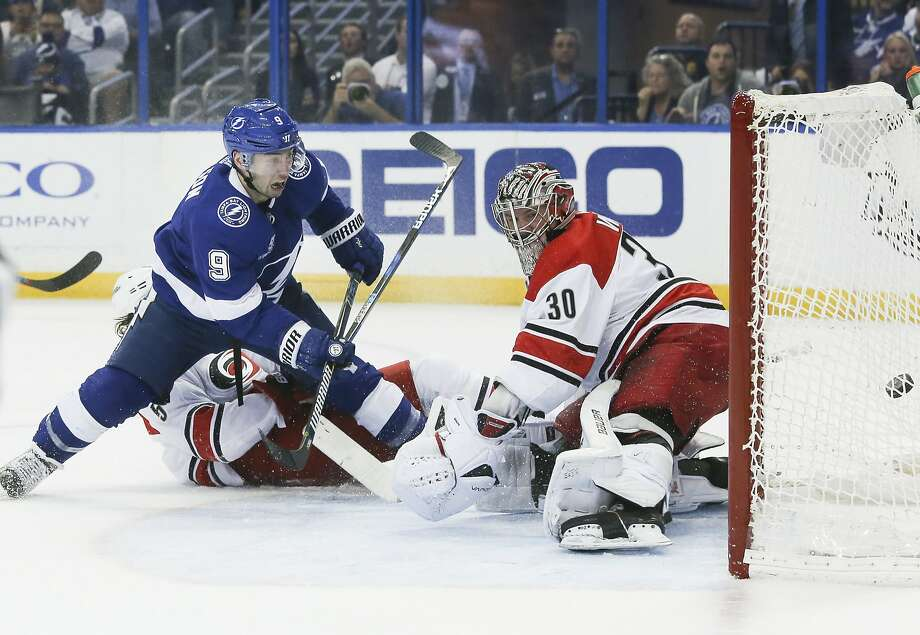 Tampa Bay's Tyler Johnson (9) beats Carolina's Noah Hanifin (5) and goaltender Cam Ward (30) to complete his hat trick. Photo: Dirk Shadd, TNS