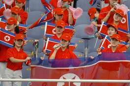 INCHEON, REPUBLIC OF KOREA:  The North Korean cheering squad wave national flags 04 September 2005.  The squad is in Incheon to support their athletes at the 16th Asian Athletics Championships.  AFP PHOTO/KIM JAE-HWAN  (Photo credit should read KIM JAE-HWAN/AFP/Getty Images)
