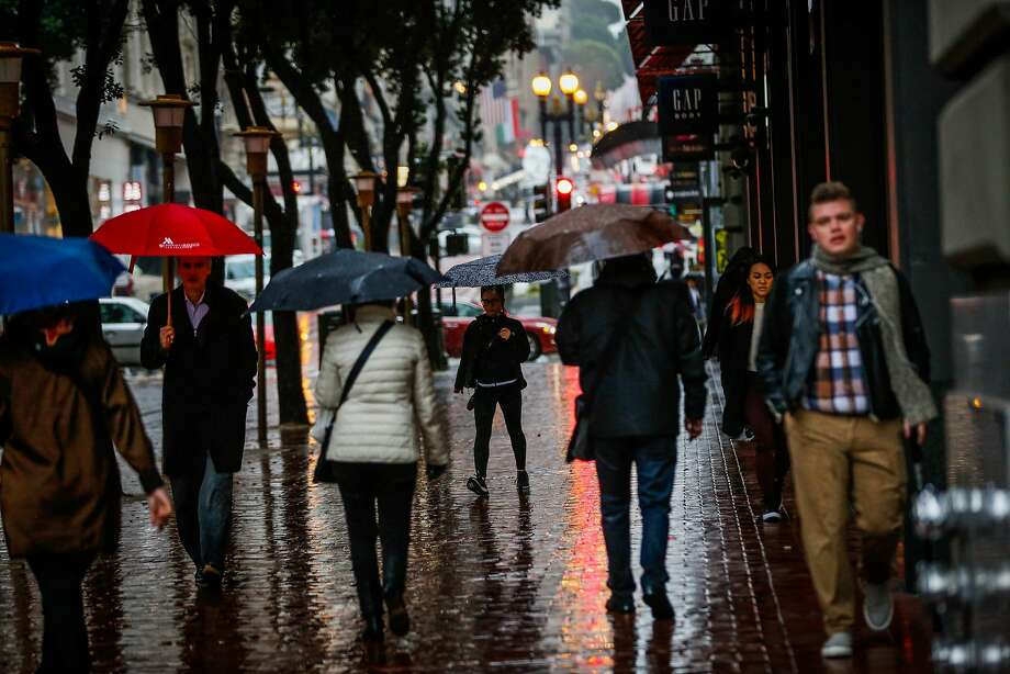 People walk down Powell Street during a rainstorm in San Francisco on Monday. Photo: Gabrielle Lurie, The Chronicle