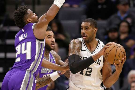 Sacramento Kings' Buddy Hield, left, and Willie Cauley-Stein, center, pressure San Antonio Spurs forward LaMarcus Aldridge during the first quarter of an NBA basketball game Monday, Jan. 8, 2018, in Sacramento, Calif.