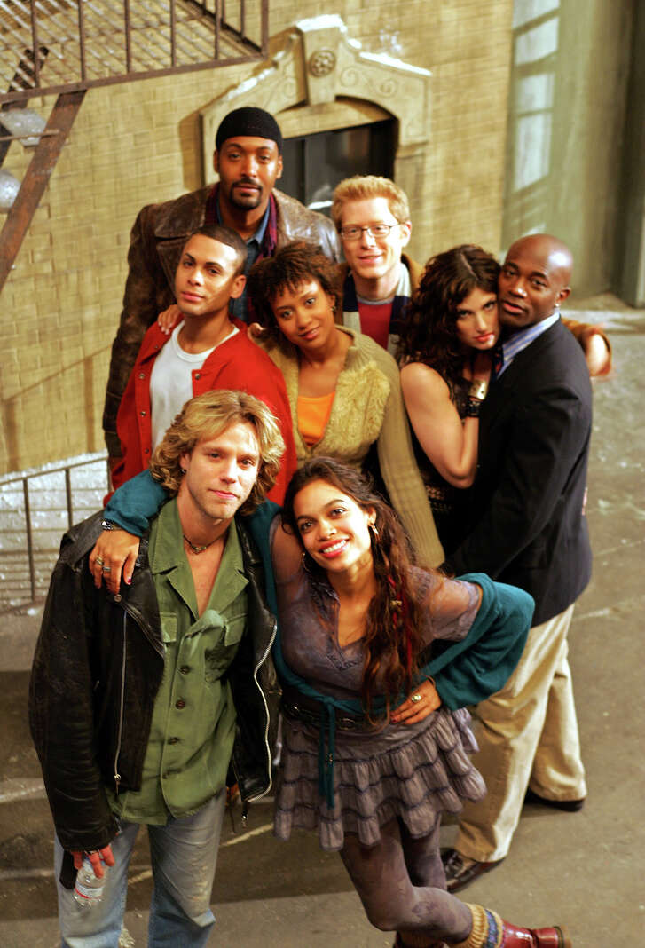 """The cast of the film """"Rent"""", front row from left, Adam Pascal, Rosario Dawson, second row from left, Wilson Jermaine Heredia, Tracie Thoms, Idina Menzel, and Taye Diggs, third row from left, Jesse Martin, and Anthony Rapp, pose for a photo  (AP Photo/Eric Risberg, file)"""