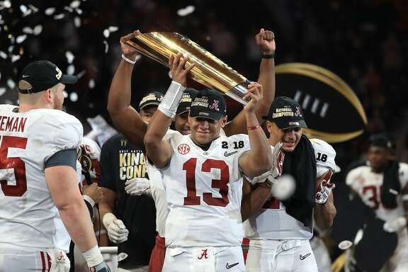 ATLANTA, GA - JANUARY 08: Tua Tagovailoa #13 of the Alabama Crimson Tide holds the trophy while celebrating with his team after defeating the Georgia Bulldogs in overtime to win the CFP National Championship presented by AT&T at Mercedes-Benz Stadium on January 8, 2018 in Atlanta, Georgia.  (Photo by Mike Ehrmann/Getty Images)