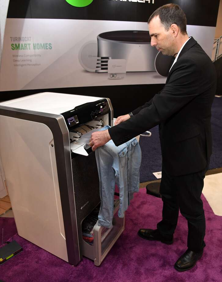 FoldiMate Founder and CEO Gal Rozov demonstrates using the FoldiMate during CES 2018 at the Sands Expo and Convention Center on January 9, 2018 in Las Vegas, Nevada. The USD 980 robotic laundry folder can handle clothing from sizes ranging from a 4-year-old's up to double X and can fold a load of laundry in under four minutes. It is expected to be available at the end of 2019. CES, the world's largest annual consumer technology trade show, runs through January 12 and features about 3,900 exhibitors showing off their latest products and services to more than 170,000 attendees. Photo: Ethan Miller/Getty Images