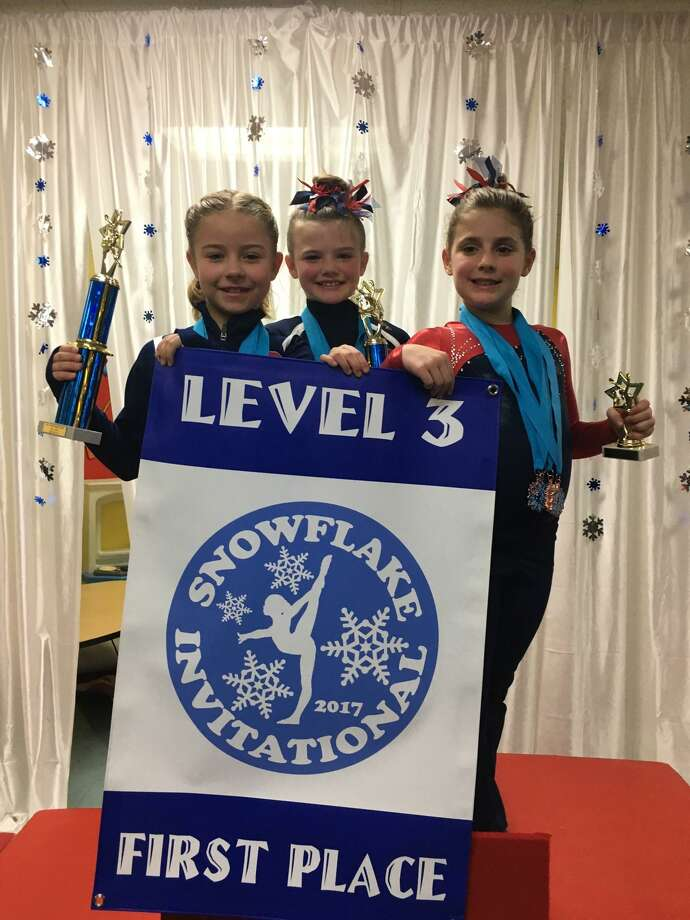 Darien YMCA Level 3 gymnasts proudly displaying their trophies and the Snowflake Invitational Level 3 team championship banner were Taylor Davies, Avery Hansen and Penelope Hahn. Photo: Contributed Photo / Darien News contributed