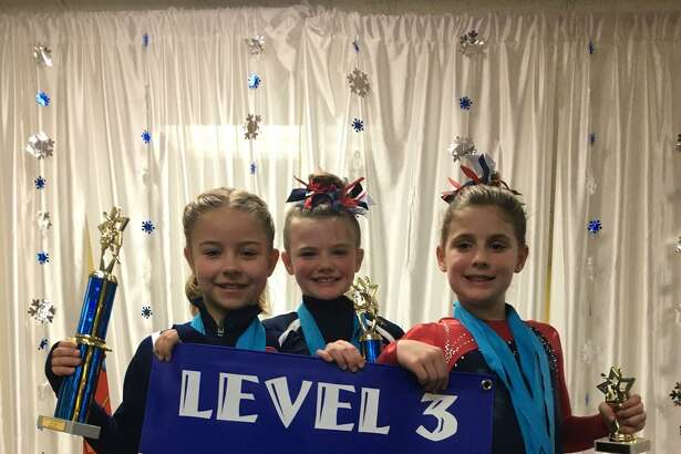 Darien YMCA Level 3 gymnasts proudly displaying their trophies and the Snowflake Invitational Level 3 team championship banner were Taylor Davies, Avery Hansen and Penelope Hahn.