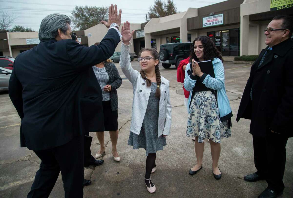 Kimberly Rodriguez high-fives David Medina, left, which is one of the family's lawyer and former Justice of the nine-member Texas Supreme Court, Wednesday, Jan. 10, 2018, in Houston.