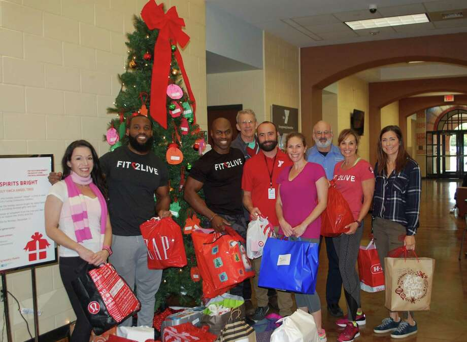 Clients and trainers from Southside's Fit 2 Live personal training gym sponsored 24 children whose families were part of the Weekley YMCA's Making Spirits Bright holiday giving program. Delivering gifts that included clothes, games, dollhouses and sports equipment are trainers from left, Victoria Lalinde, Jermaine Patterson and gym owner Tony Hood.  Representing the Weekley YMCA are board member Dave Agerton and Director of Outreach, Shawn McGown. Clients include Rachel Brays, David Leva, Julie Stein and Jennifer Lerner. Photo: Fit 2 Live