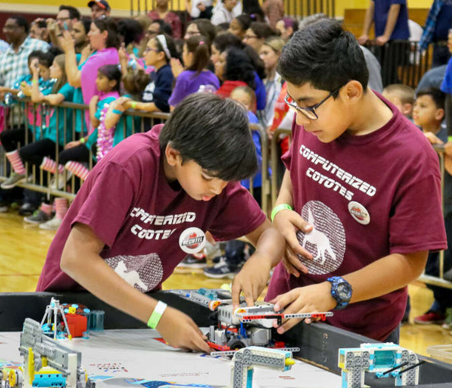 Kartik Rai(L) and Derek Elis (R) from the Beck Junior High Computerized Coyotes, change out a part on their robot before re-starting it on a second pre-programmed mission. The rookie team is one of six teams from the Katy Qualifier advancing to next January's FIRST LEGO League Texas South Region Championship Tournament. Photo: CRHS-CRyptonite