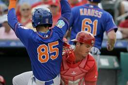 New York Mets' Luis Guillorme (85) scores ahead of the tag from St. Louis Cardinals catcher Mike Ohlman during the sixth inning of an exhibition spring training baseball game Monday, March 7, 2016, in Jupiter, Fla. (AP Photo/Jeff Roberson)