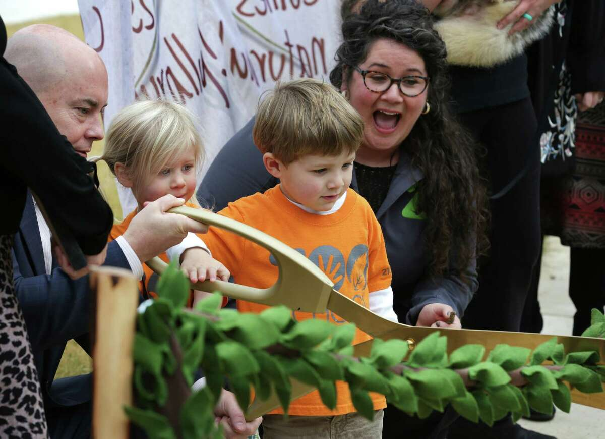 San Antonio Zoo CEO Tim Morrow, left, helps students Leora Latimer, second from left, and Will Russell, with teacher Sarah Mortati, right, cut the