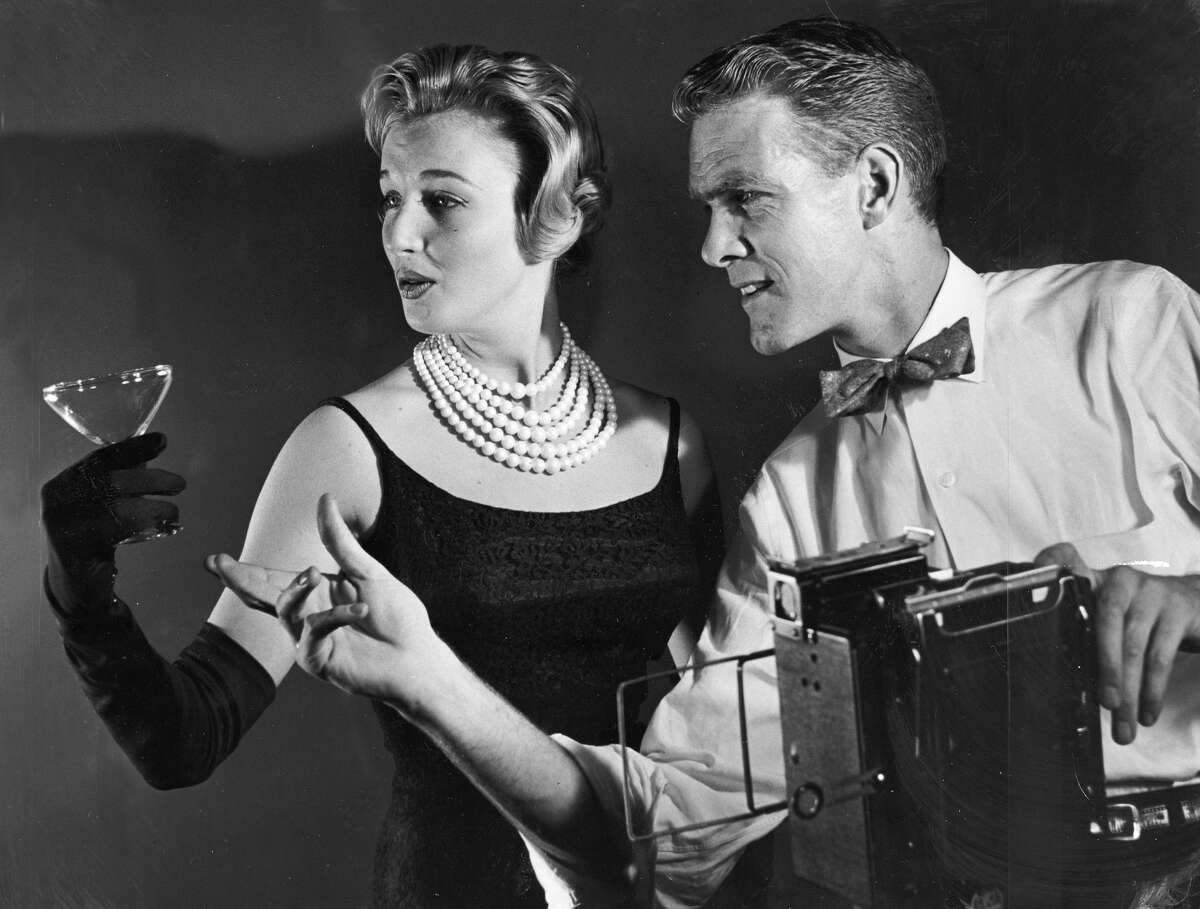 Lynn Maidment (L), a model from the Kathleen Peck modeling agency, poses for Seattle P-I photographer John Vallentyne (R), who also poses for Seattle P-I photographer Tom Brownell in this 1959 photograph by Brownell.