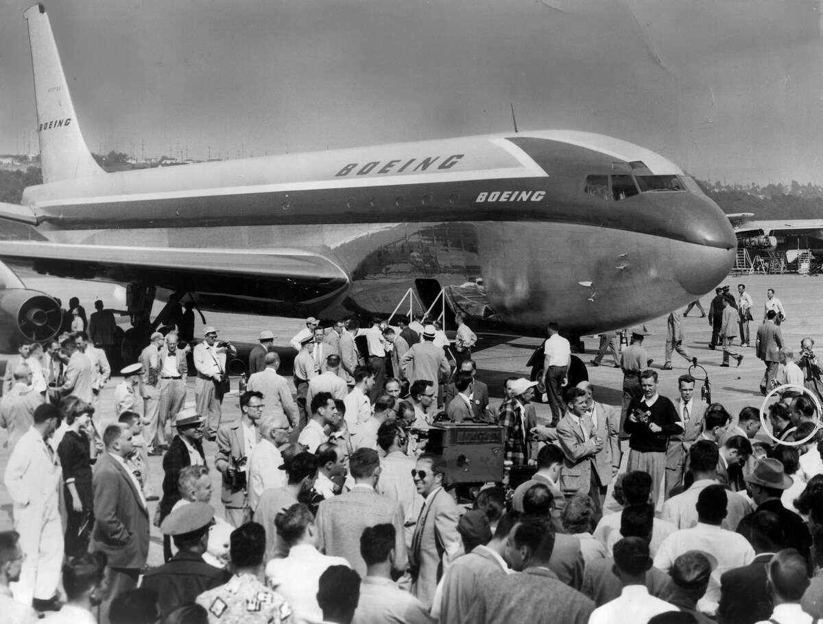 Test pilots, in circle at right, are surrounded by reporters, photographers and well-wishers after completion of the epochal flight of the Boeing 707 at Seattle's Boeing Field. The huge, sleek jet transport made a successful one-hour and 24-minute test flight in 1954.