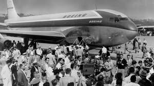 Test pilots, in circle at right, are surrounded by reporters, photographers and well-wishers after completion of epochal flight at Seattle's Boeing Field.  The huge, sleek 707 jet transport, which made a successful 1-hour and 24-minute test flight forms the backdrop for the thong. -1954