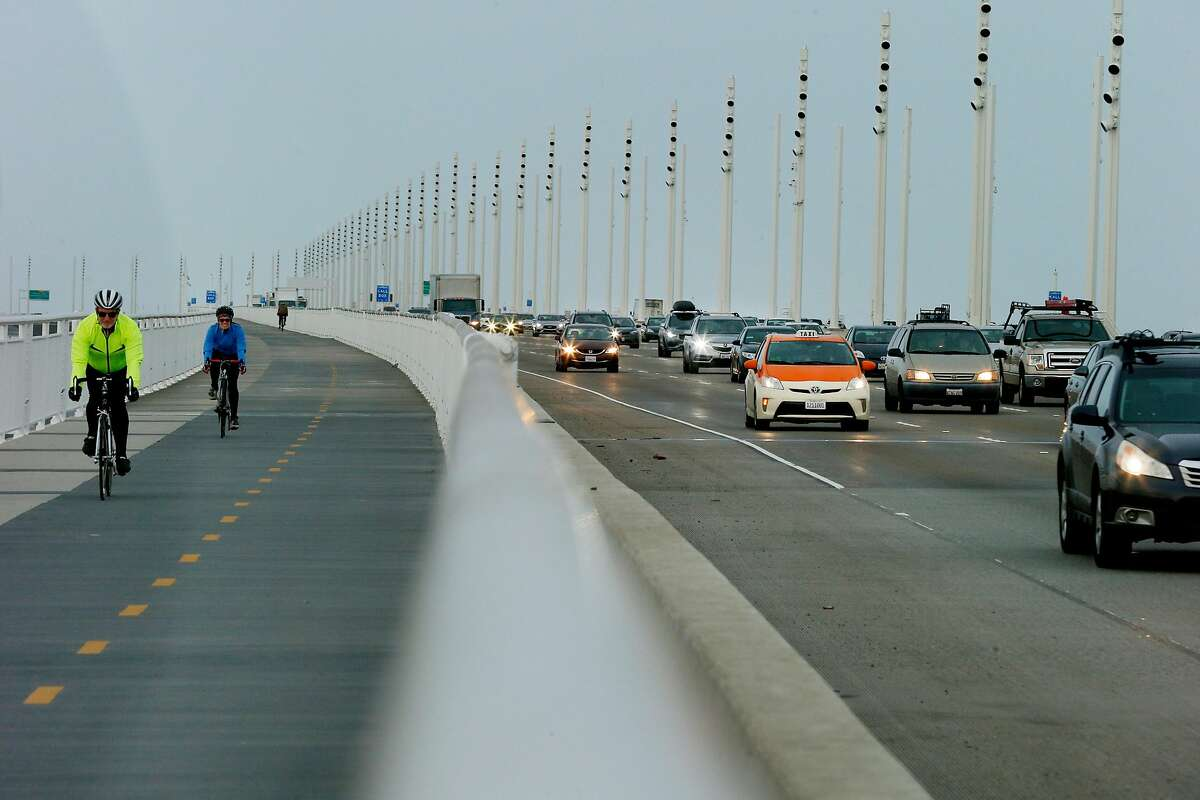 Commuters and bicyclists cross the Bay Bridge Wednesday. Revenue from proposed toll increases would go toward transit and roadway improvements.