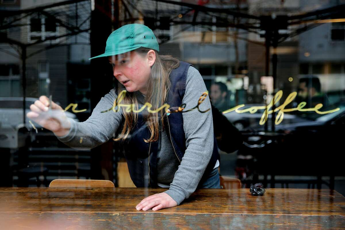 Sarah Jane Bouldin removes the Four Barrel Coffee name from the front window, Wednesday, Jan. 10, 2018, in San Francisco. Days after the S.F. Chronicle's investigative piece surrounding a sexual harassment lawsuit filed against Four Barrel and the company's founder Jeremy Tooker, the embattled coffee roaster has announced it will change its name and plans to transition into an entity that's 100 percent employee-owned. Four Barrel had announced that it would temporarily change its name to the Tide, but now it is changing it back.