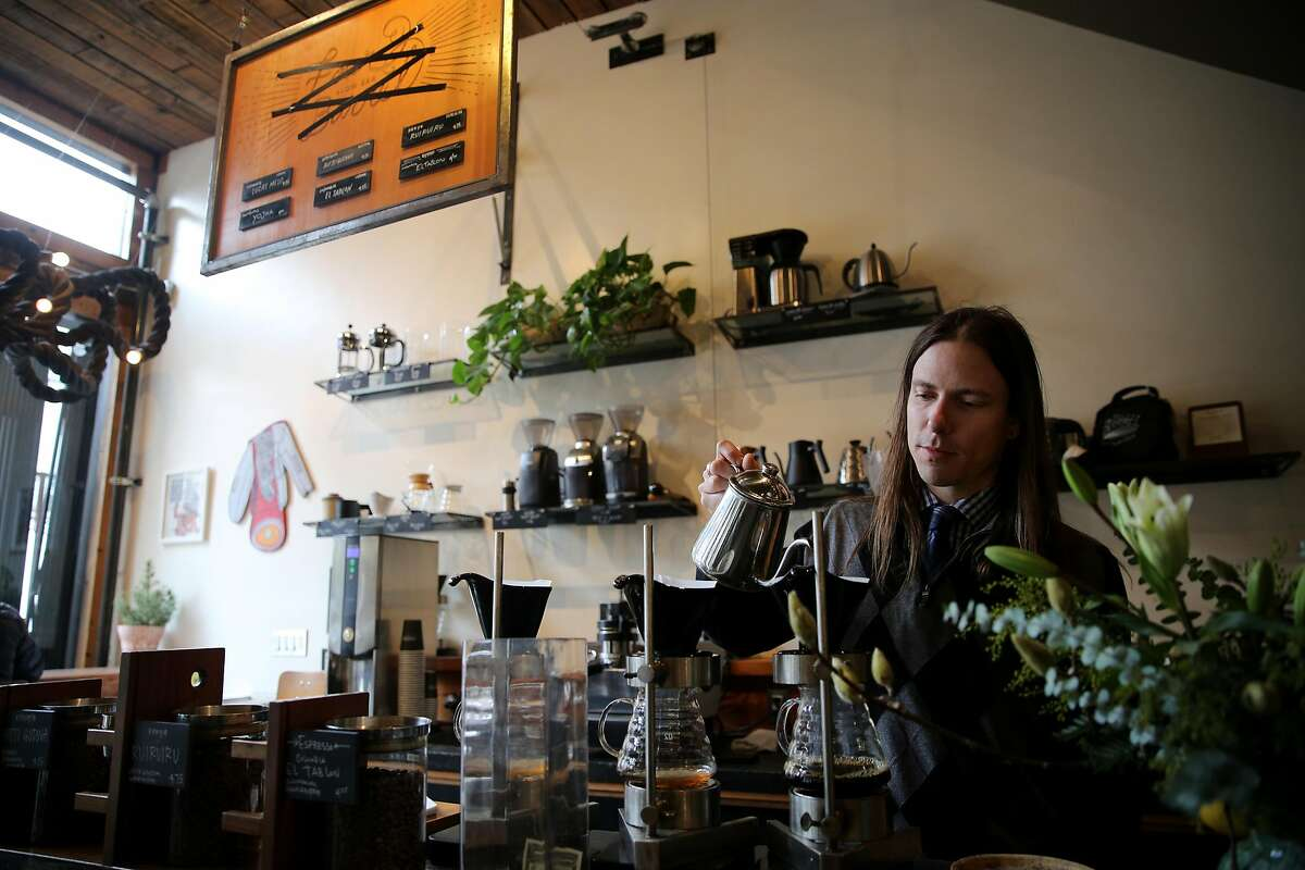 Justin Teisl, a barista and art curator, makes a customer's coffee as the name of the Four Barrel Coffee menu is seen crossed out (above), Wednesday, Jan. 10, 2018, in San Francisco, Calif.