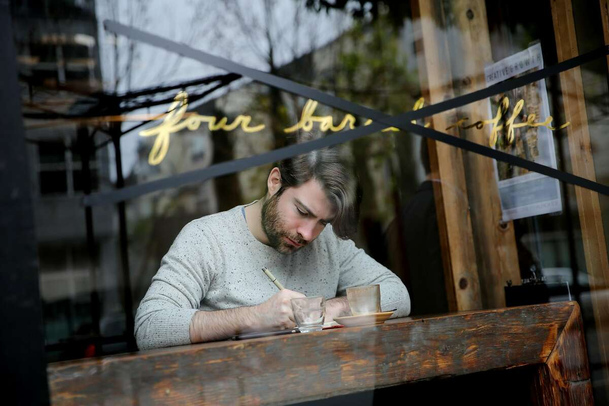 Drew Winget, a regular customer at Four Barrel Coffee, is shown on Jan. 10 after the company's window-display name was crossed out by employees. Four Barrel had announced that it would temporarily change its name to the Tide, but now it is changing it back.