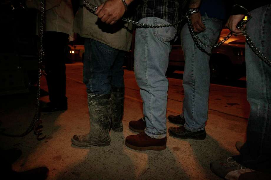 Men chained together wait for a jail van in northeast Houston. HPD arrested more buyers than prostituted individuals last year. Photo: Julio Cortez, Staff / Houston Chronicle