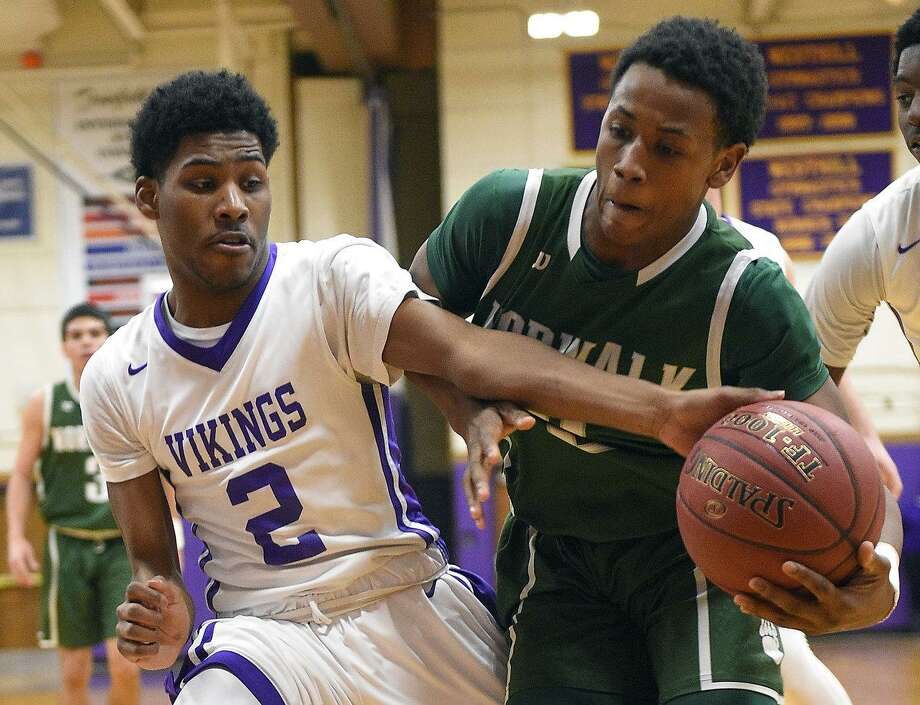 Westhill's Rashawn Gibson, left, (2) tries to knock the ball away from Norwalk's Zyaire Sellers on Tuesday night in Stamford. Photo: Matthew Brown / Hearst Connecticut Media / Stamford Advocate