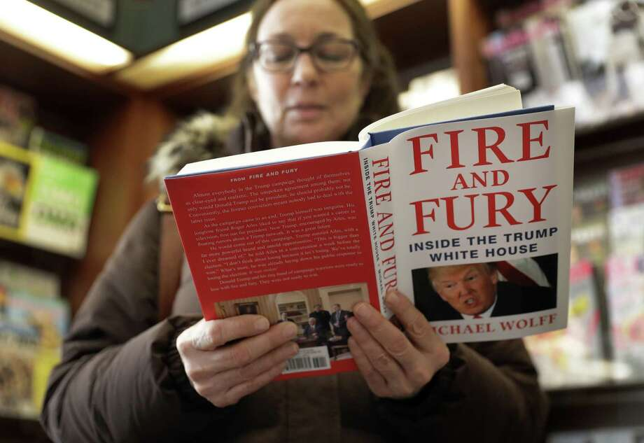"""Kathy Mallin, from Glenview, Ill., looks over a copy of the book """"Fire and Fury: Inside the Trump White House"""" by Michael Wolff at Barbara's Books Store Friday in Chicago. The book signals a descent into lowbrowism in the anti-Trump movement. Photo: Charles Rex Arbogast /Associated Press / Copyright 2018 The Associated Press. All rights reserved."""