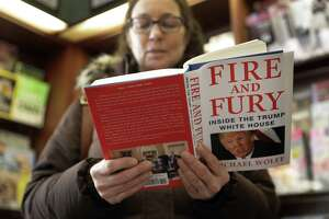"""Kathy Mallin, from Glenview, Ill., looks over a copy of the book """"Fire and Fury: Inside the Trump White House"""" by Michael Wolff at Barbara's Books Store Friday in Chicago. The book signals a descent into lowbrowism in the anti-Trump movement."""