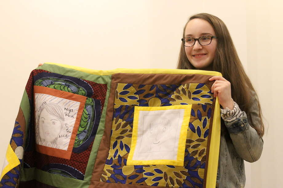 Anna Schupack, 17, a senior at Emma Willard School, poses with a quilt that will be raffled on Friday at a benefit for Refugee Immigrant Support Services of Emmaus (RISSE). (Christopher Lisio / Special to the Times Union)