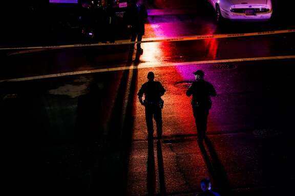 Police officers walk through a crime scene at 7th and Chester Streets outside the West Oakland Bart Station after a shooting in Oakland, Calif., on Wednesday, Jan. 3, 2018. Sahleem Tindle was killed by police during an incident involving another man.