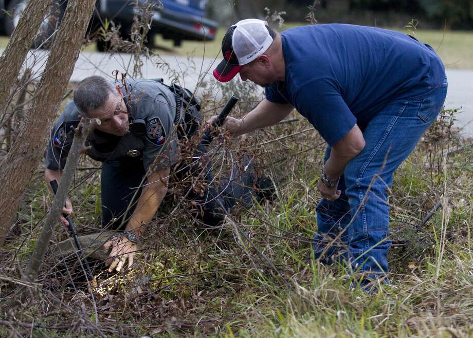 An officer with the Montgomery County Precinct 4 Constable's Office searches a drainage ditch for a weapon near the home of a student who stabbed a 13-year-old student behind White Oak Middle School by a classmate, Wednesday, Jan. 10, 2018, in Porter. Photo: Jason Fochtman/Houston Chronicle