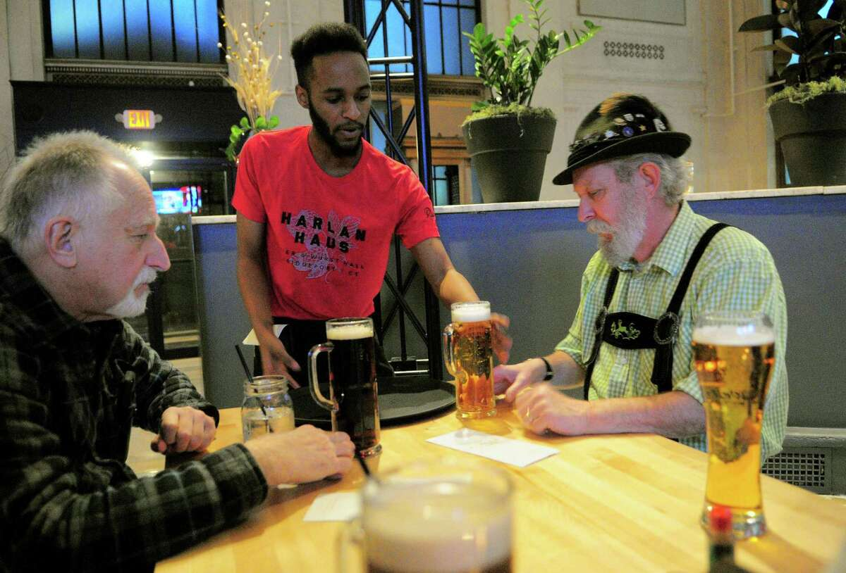 Waiter Leon Jefferson brings beer to Tom Fraher, of Bridgeport, right, and his friend Tony Longo during the grand opening of Harlan Haus, a new beer hall and restaurant on State Street in downtown Bridgeport, Conn., on Tuesday Jan. 10, 2018.