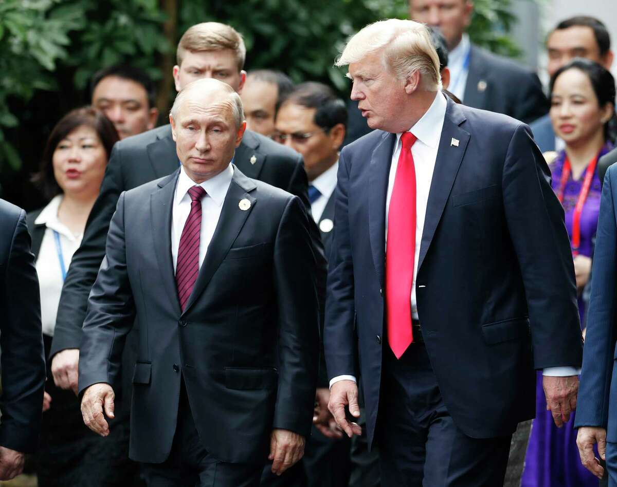 FILE - In this Nov. 11, 2017, file photo President Donald Trump, right, and Russia's President Vladimir Putin talk during the family photo session at the APEC Summit in Danang, Vietnam. A sweeping new report by congressional Democrats warns of deepening Russian interference throughout Europe and concludes that even as some Western democracies have responded with aggressive counter-measures, Trump has offered no strategic plan to bolster their efforts or safeguard the U.S. from again falling victim to the KremlinÂ?'s systematic meddling. The 200-plus page report released by Sen. Ben Cardin, D-Md., the ranking Democrat on the Senate Foreign Relations Committee, comes without sign-off from Republicans on the panel. (Jorge Silva/Pool Photo via AP, File)